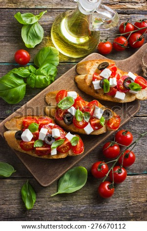 bruschetta with tomato, feta cheese, olives and basil, top view - stock photo