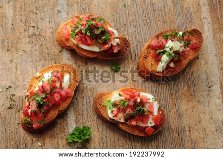 Bruschetta with tomato, mozzarella cheese, garlic and herbs  - stock photo