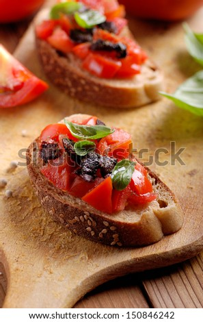 bruschetta with tomato, olives and basil - stock photo