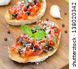 bruschetta with tomato, olives, basil and cheese on a wooden board close-up - stock photo