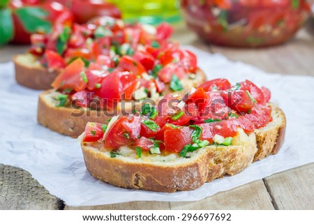 Bruschetta with tomatoes, herbs and oil on toasted garlic cheese bread - stock photo