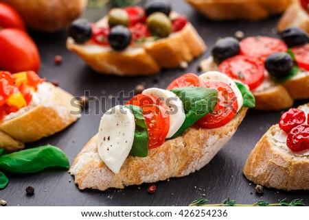 Bruschetta with tomatoes, mozzarella and basil - stock photo
