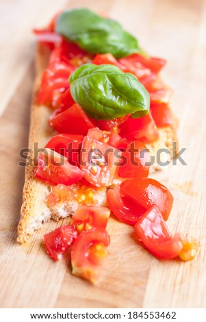 Bruschetta with tomatoes on a cutting borad, isolated - stock photo