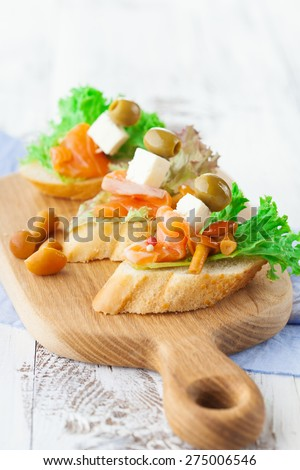 Bruschettas with cheese, smoked salmon and salad on crusty bread on white wooden background, selective focus