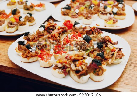Bruschettas with meat, vegetables and soft cheese, toned image