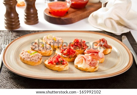 Bruschette with tomatoes, tuna and prosciutto - stock photo