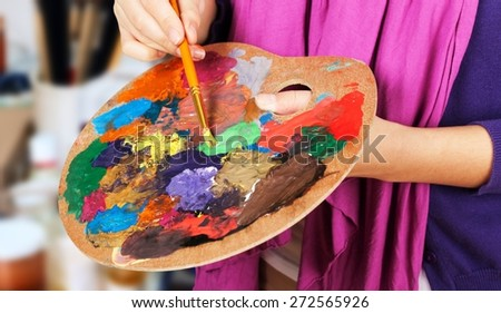 Brush. Artist brush mix color oil painting on palette is holding in his hand closeup - stock photo