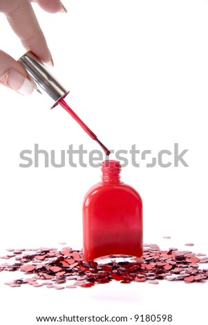 brush of nail polish in fingers and sparkles around - stock photo