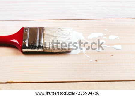 Brush painting wooden furniture with white color, close up - stock photo