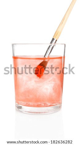Brush with color paint in glass of water, isolated on white
