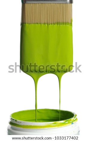 Brush with green paint dripping isolated on a white background