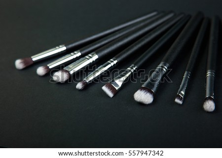 Brush with natural bristles for professional makeup, closeup, cosmetics, makeup, black background, natural cloth