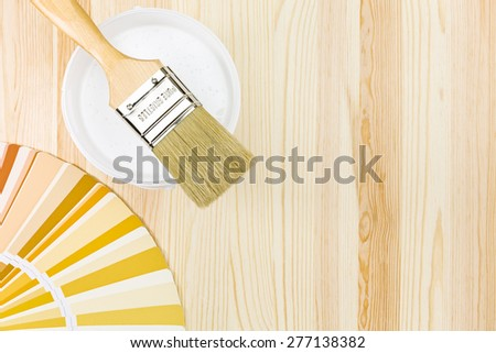 brush with paint can and color samples on wooden background - stock photo