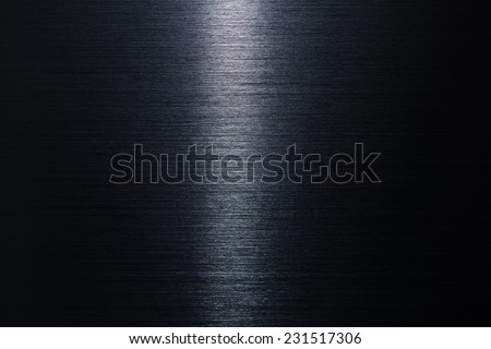 Brushed metal texture in the dark with narrow lighting in middle.  - stock photo