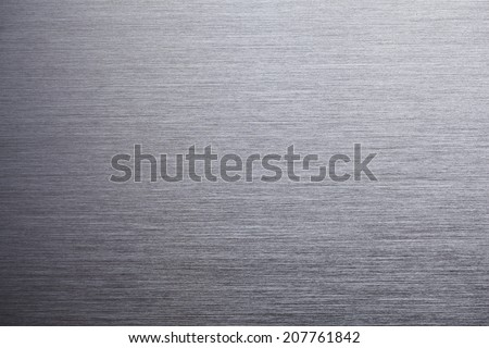 Brushed metal texture, shadow on lower left. - stock photo