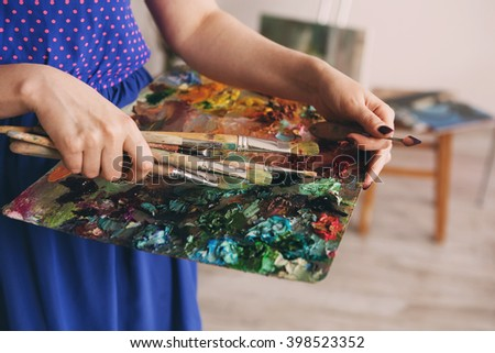 brushes and oil paints on palette.  artist's palette, texture mixed oil paints. palette with paintbrush and palette-knife in artist??s hands. The girl artist holding a palette with oil paints - stock photo