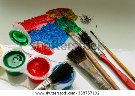 Brushes and paint on white artist made a few strokes and brush left lying - stock photo