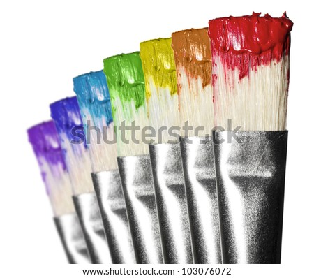 Brushes in rainbow color paint in white background - stock photo