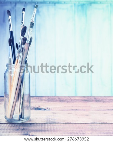 Brushes on wooden background toned with free space. Toned in blues. - stock photo