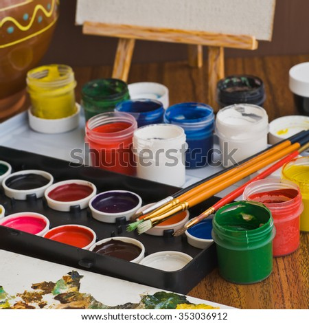 Brushes, paint and other supplies for drawing lessons at school. Selective focus
