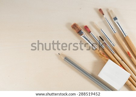brushes , pens, rubber and pencil on wooden background - stock photo