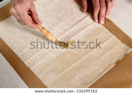 Brushing sheet of filo pastry with melted butter. Making Filo Pastry Topped Apple Pie Series.