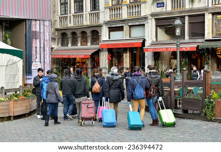 BRUSSELS, BELGIUM-DECEMBER 8, 2014: Leaving Brussels tourists came back one time again to see Grand Place - stock photo