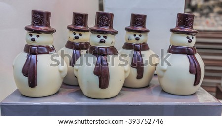 Brussels, Belgium - January 17 2015: White and milk chocolate snowmen in the Leonidas store window at Christmas. Leonidas is a Belgian chocolate company with 350 shops in Belgium and 1250 in the world - stock photo