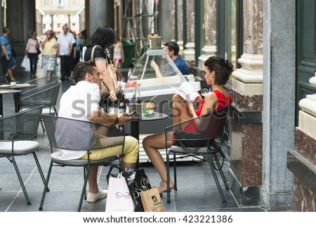 BRUSSELS, BELGIUM - JULY 4, 2015: A couple talk, sitting in a coffee shop in the Galeries Royales Saint Hubert, in the city center, the first commercial galleries of Europe. - stock photo