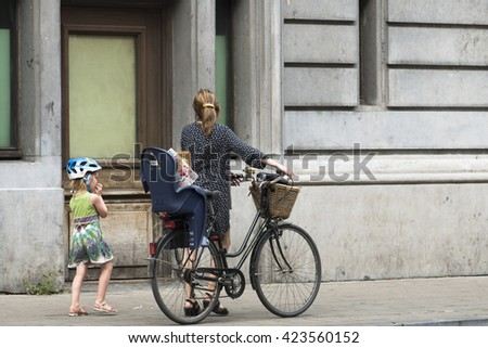 BRUSSELS, BELGIUM - JULY 4, 2015: A woman wearing a bicycle rides with your children by one of the streets of the city. - stock photo
