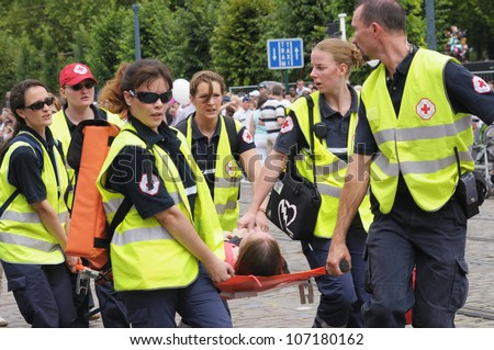 BRUSSELS, BELGIUM - JULY, 21: Belgian Red Cross team helps to person with sunstroke during National Day of Belgium on July 21, 2009 in Brussels. Well trained and equipped teams were on duty this day - stock photo
