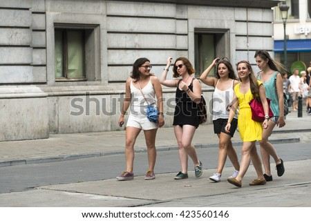 BRUSSELS, BELGIUM - JULY 4, 2015: Five young women chatting while walking through one of the streets of the city. - stock photo