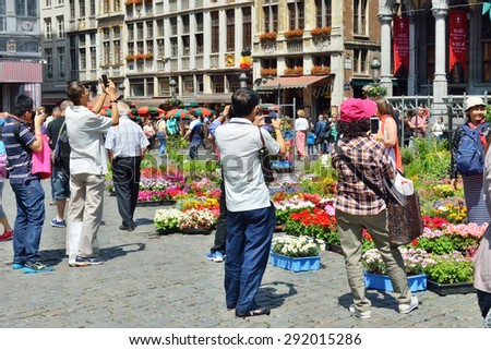 BRUSSELS, BELGIUM-JUNE 06, 2015: Foreign tourists take pictures of Grand Place in Brussels, one of mostly photographed places in the world - stock photo