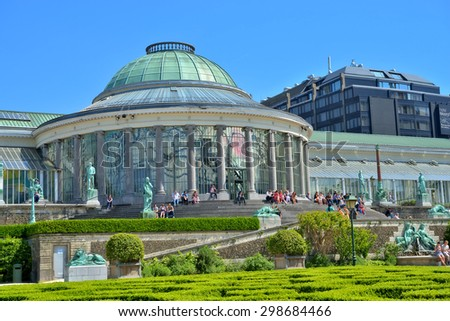 BRUSSELS, BELGIUM-JUNE 06, 2013: People sit around exhibition building in Botanique garden during lunch time - stock photo