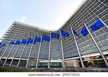 BRUSSELS, BELGIUM - MARCH 16: EU flags blown by wind in front of the European Commission Headquarters, also know as the Berlaymont building, on March 16, 2016 in Brussels.