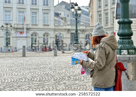 BRUSSELS, BELGIUM-MARCH 06, 2015: Young tourist reads map of Brussels in historical center of city - stock photo