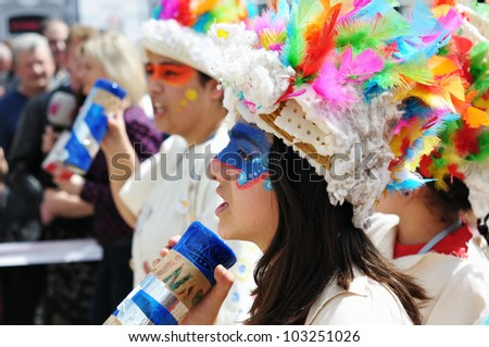 BRUSSELS, BELGIUM-MAY 19: An unknown participant with colored face greets visitors during Zinneke Parade on May 19, 2012 in Brussels. This parade is a biennial urban artistic and free-attendance event - stock photo