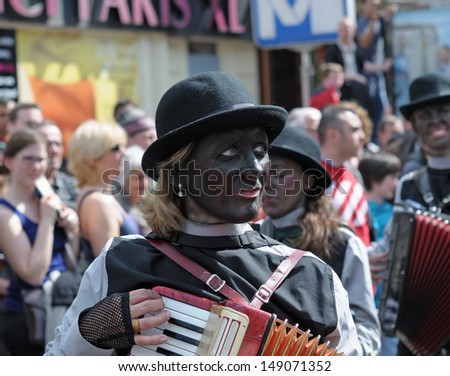 BRUSSELS, BELGIUM-MAY 19: An unknown participant with colored face plays music during Zinneke Parade on May 19, 2012 in Brussels. This parade is a biennial free-attendance and attracted many tourists