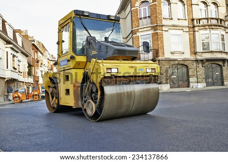 BRUSSELS, BELGIUM - NOVEMBER 29, 2014:  Heavy Vibration roller compactor at asphalt pavement works for road repairing on November 29, 2014 in Brussels, Belgium - stock photo