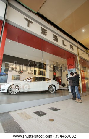 BRUSSELS, BELGIUM, WEDNESDAY, MARCH 9, 2016: Pedestrians walk past a showroom of Tesla Motors, Inc. Tesla produces high-end electric cars. - stock photo