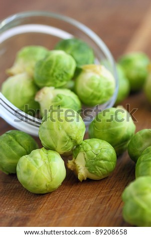 Brussels sprout in a glass bowl on wooden table - stock photo