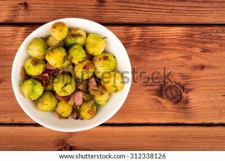 Brussels sprouts fried with ham and onion on the wooden background. - stock photo