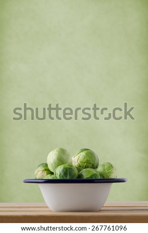 Brussels sprouts, piled into an enamel cooking tin, on wood planked kitchen table against pale green textured wall with copy space above. - stock photo