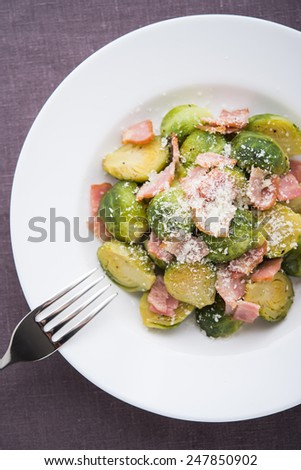 Brussels sprouts with bacon on dark background top view. - stock photo