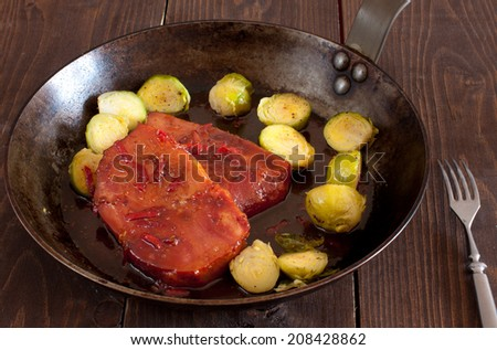 Brussels sprouts with smoked pork chops with chili and glazed with honey and orange juice - stock photo