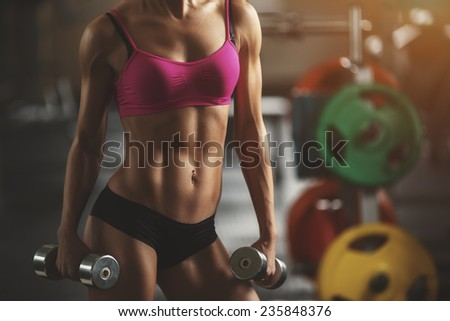 Brutal athletic fitness woman pumping up muscles with dumbbells. Part of fitness body. Attractive fitness woman, trained body, fitness model. Fitness woman in the gym. Fitness woman with dumbbell. - stock photo