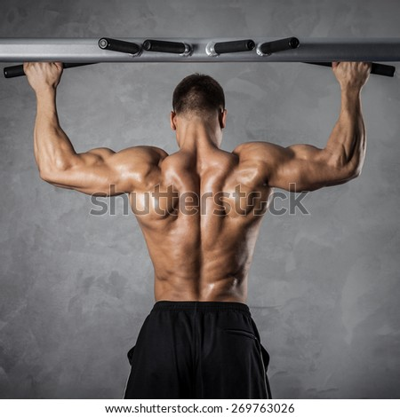 Brutal athletic man making pull-up exercises on a crossbar - stock photo