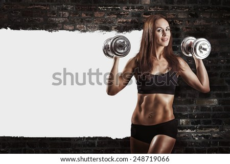 Brutal athletic woman pumping up muscules with dumbbells. White area - stock photo