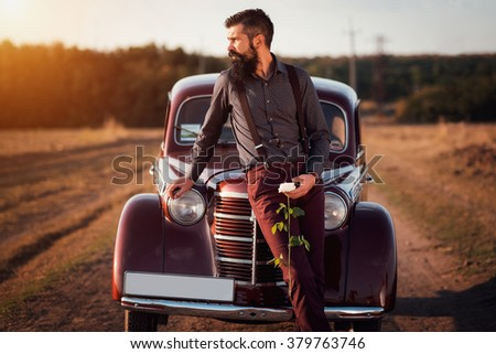 brutal bearded man with a mustache in a shirt, pants with suspenders stands leaning on the hood of a retro car holding a white rose and looking at the sunset - stock photo