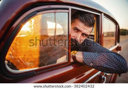 brutal bearded man with a mustache in a shirt, pants with suspenders with a girl with dark hair and big lips with bright red lipstick in a short dress and heels near retro car at sunset - stock photo